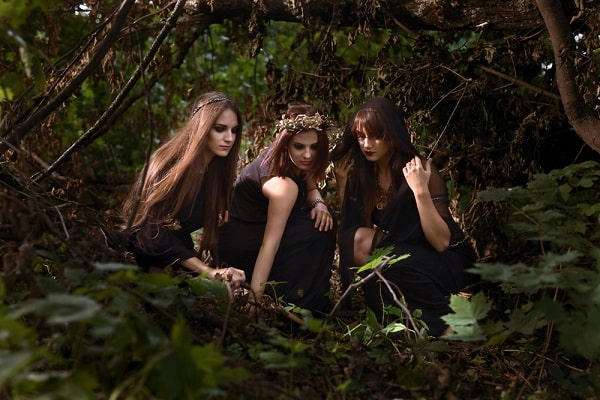 Three long-haired women dressed as witches in a forest for Halloween.