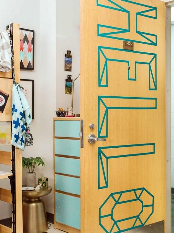 A dorm room with a personalized door greeting using blue washi tape.