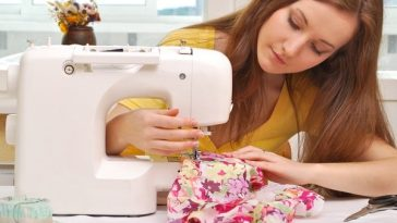 A young woman in a yellow shirt, making a dress with a sewing machine.