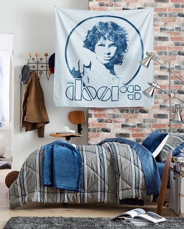 A guy's dorm room with a rock and roll style achieved by a photo tapestry of The Doors, cool-toned beddings, and a brick-style accent wall.