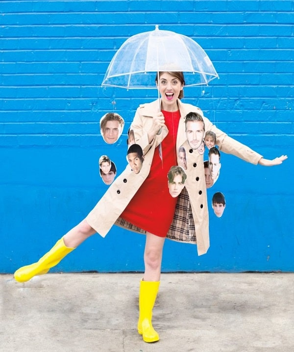 A woman wearing an It's Raining Men costume made of a clear bubble umbrella with dangling cut-out photos of male celebrities hung by a nylon string.