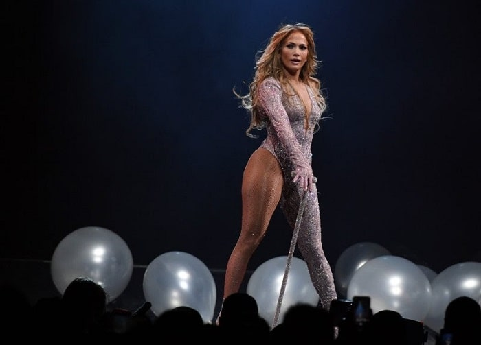 Jennifer Lopez onstage in a sparkly one-piece outfit and long wavy ombre-colored hair.