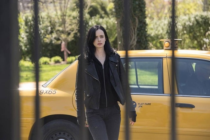 Jessica Jones from the TV series Jessica Jones, wearing her black hoodie underneath a black leather jacket, with matching black fingerless gloves.
