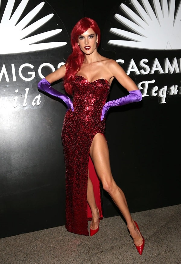 Alessandra Ambrosio in a Jessica Rabbit costume, wearing her iconic red gown and purple gloves.