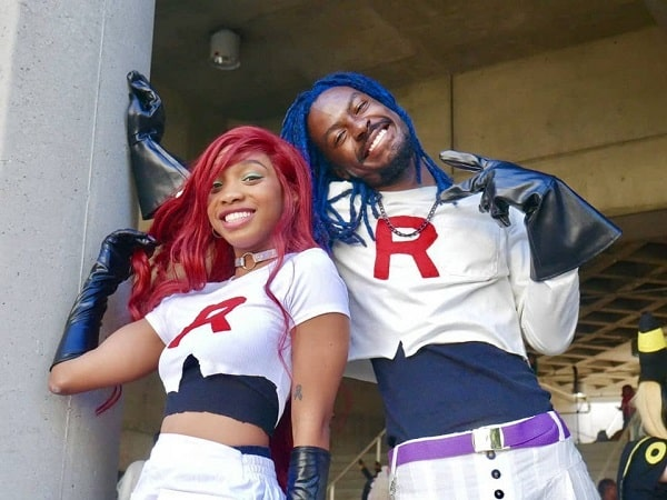 A woman and a man in Jessie and James of Team Rocket costumes, inspired by Pokémon.