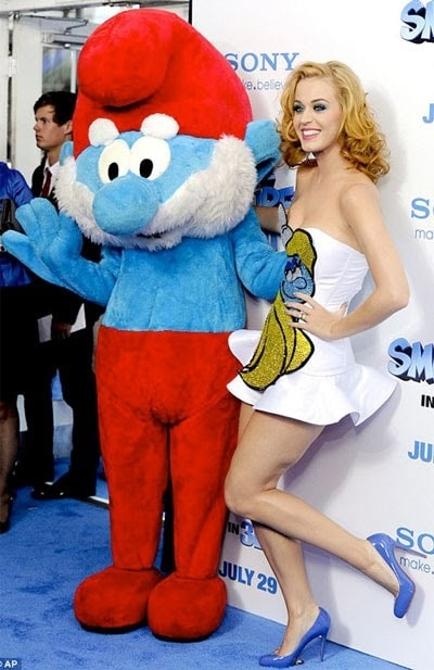 Katy Perry wearing a white dress with a Smurf patch, with blue platform pumps.