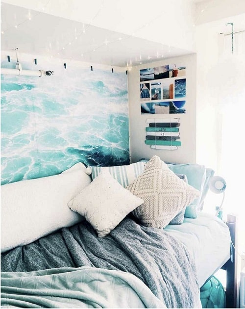 A dorm room with a beach tapestry, along with light blue and taupe sheets and throw pillows.