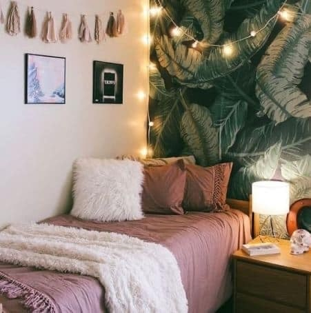 A dorm room with a tropical green wall accent and warm white string lights.