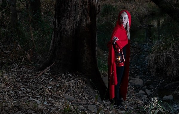A blonde woman in a red riding hood costume, holding a lamp in the woods.