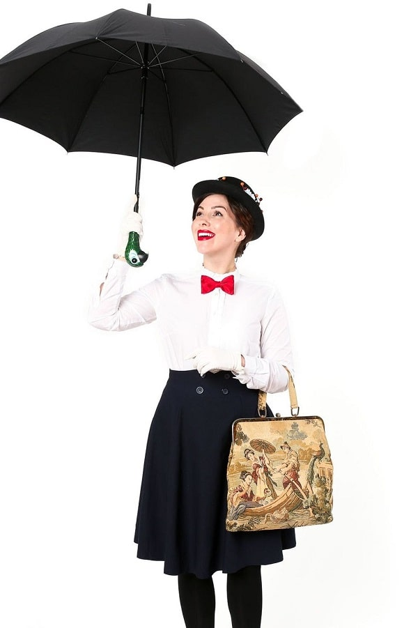 A woman in a Mary Poppins costume, wearing a white shirt, black shirt, and red bowtie, hat, complete with tote bag and umbrella.