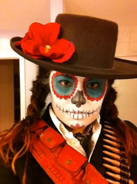 A woman wearing a señor costume for Day of the Dead, with matching black hat and ammo belt.