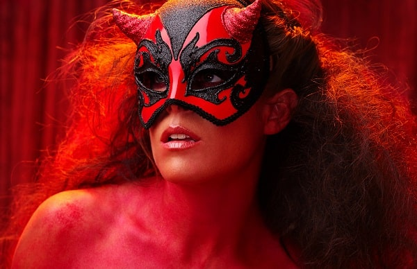 A woman in a masquerade-style devil costume, wearing a Venetian masquerade devil mask and red body paint.
