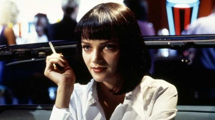A scene from the movie Pulp Fiction, with Mia Wallace in her white shirt and cigarette in hand.