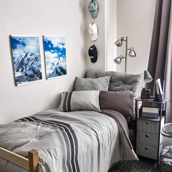 A guy's dorm room with beddings of different shades of grey with matching decor and curtain.
