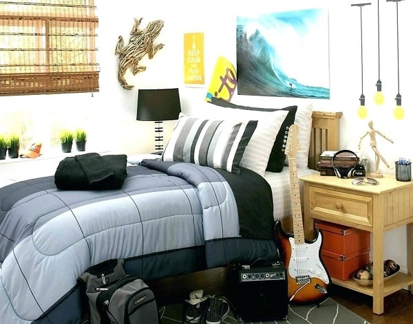 A guy's dorm room with a guitar and amp on the floor, dark-toned beddings, and wall art.