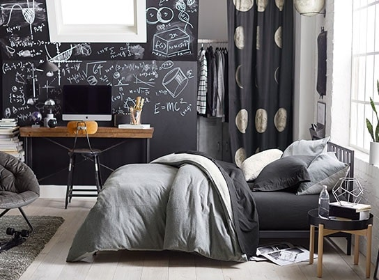 A guy's dorm room with a gray motif and a chalkboard wall that can be utilized for note taking.