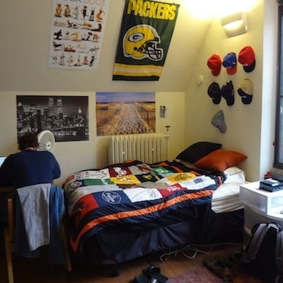 A guy's dorm room with a sports-inspired theme, decorated with baseball caps, banners, and a comforter with sports team logos.