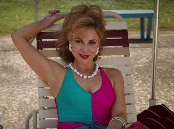 Mrs. Wheeler wearing her flirty low-cut swimsuit and white choker by the poolside in Stranger Things.