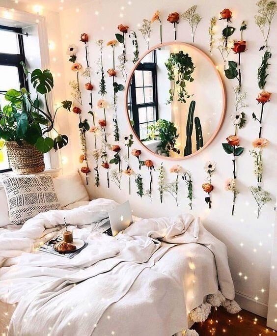 A dorm room with wall flower-vine accents, a gold circle mirror, and neutral-colored beddings.