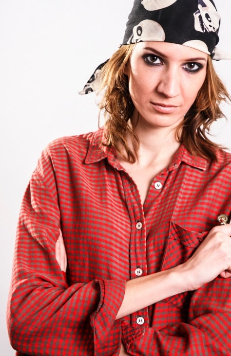 A woman wearing a not-your-average-crewmate pirate costume with a red button-up shirt and matching black and white skull bandana.