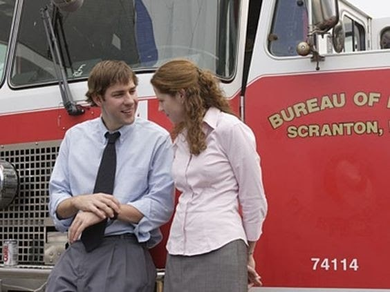 A scene from The Office with Pam talking to Jim, in her pink shirt and gray pencil skirt.