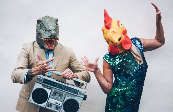 Two individuals wearing their literal party animals costume with alligator and chicken head masks.