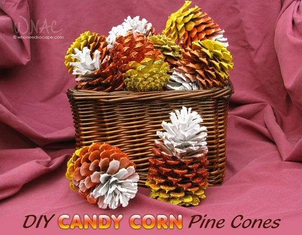 Acrylic-painted natural pine cones with a candy corn motif using red, yellow, orange, and white paint.
