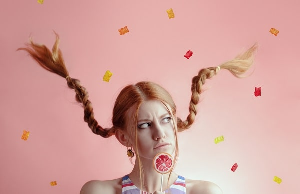 A woman in braids, holding a lollipop, with gummy bears falling from the ceiling.