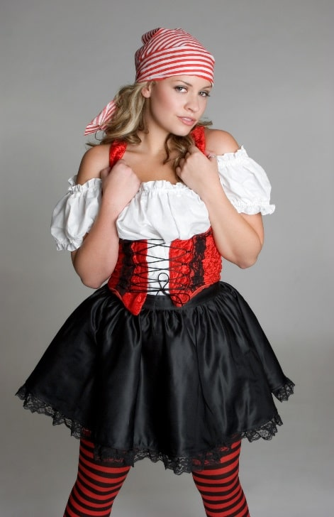 A woman in a pirate wench costume, wearing a matching red and white striped bandana.