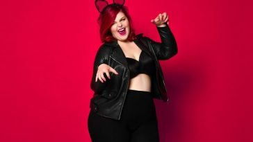 A woman in a Halloween costume, wearing a black leather jacket, matching pants, and bunny ears.