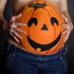 A jack-o'-lantern painted on the belly of a pregnant woman wearing jeans.