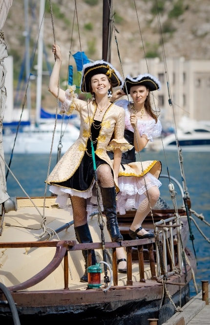 Two women in preppy pirate costumes on board a ship.