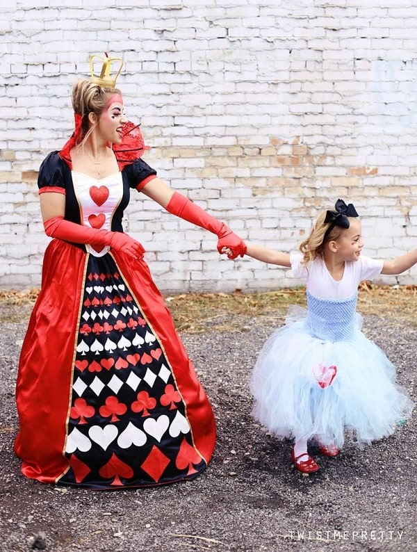 A woman wearing a red, black, and white queen of hearts gown and crown, holding little girl's hand.