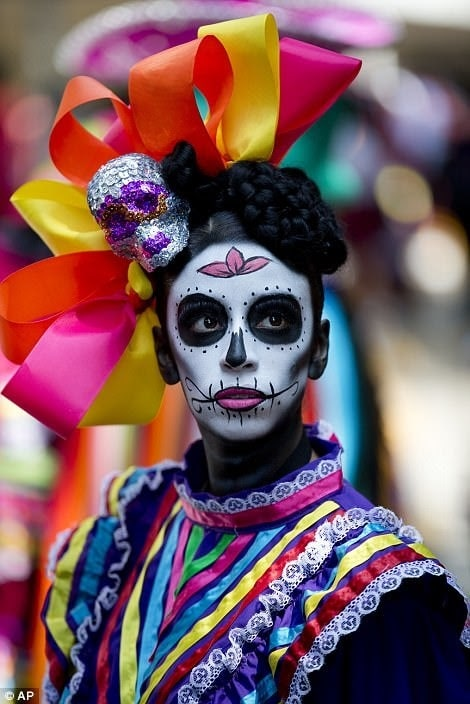 A woman dressed as a rainbow-colored La Catrina for Day of the Dead, wearing a brightly colored dress and matching headpiece.