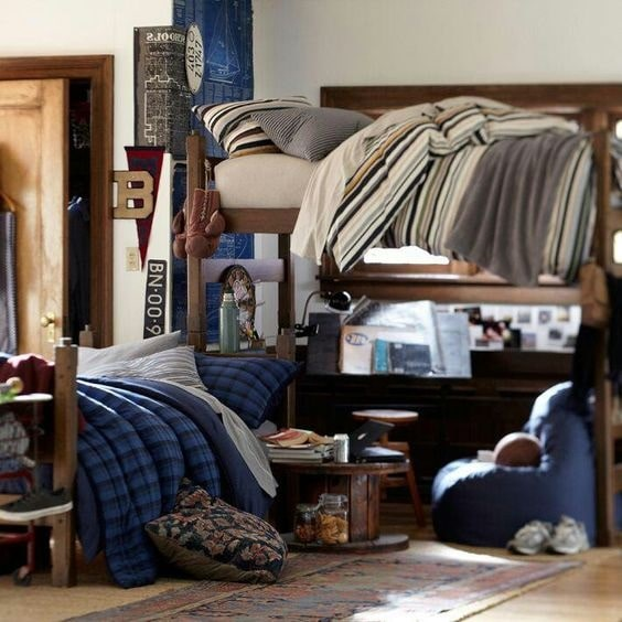 A guy's dorm room with a laidback using bunk beds with striped beddings of blue, gray, and earth tones.