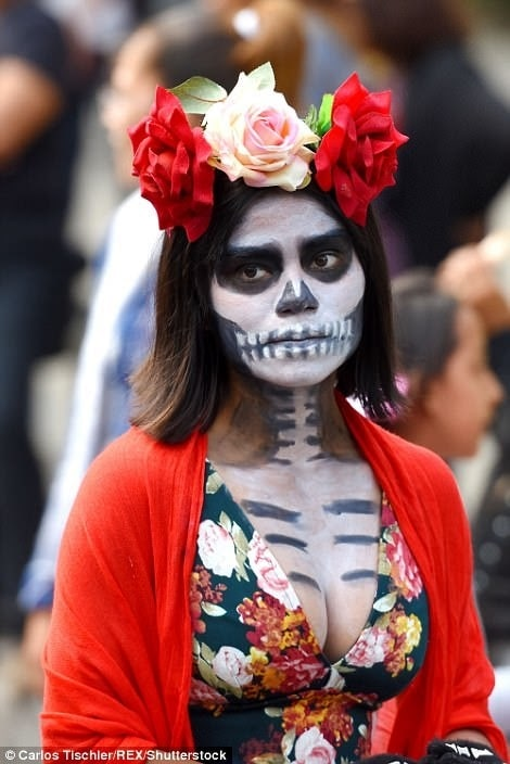 A woman in a Day of the Dead costume, wearing black and white face paint and a flower crown made of red and pink roses.