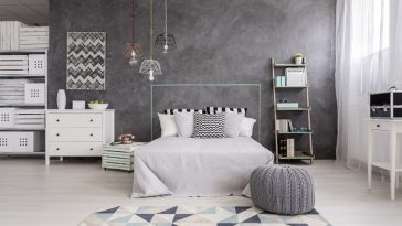 A modern rug with geometric patterns, along with a gray knit ottoman to match an industrial-style bedroom.