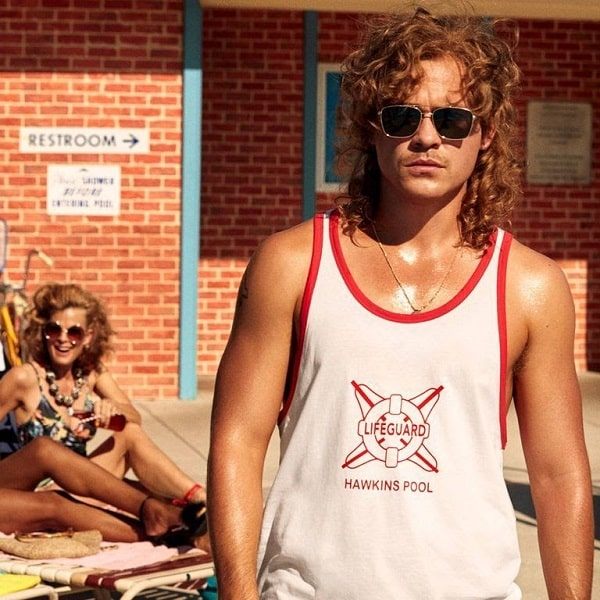 Billy Hargrove wearing his lifeguard shirt and sunglasses in Stranger Things Season 3.
