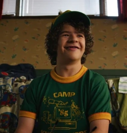 Dustin Henderson wearing his green and yellow Camp Know Where shirt and matching hat in Stranger Things Season 3.