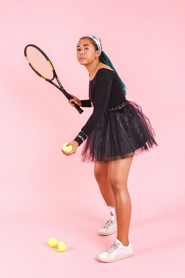 A woman in a Serena Williams costume, wearing a black leotard and matching tutu with white sweatbands.