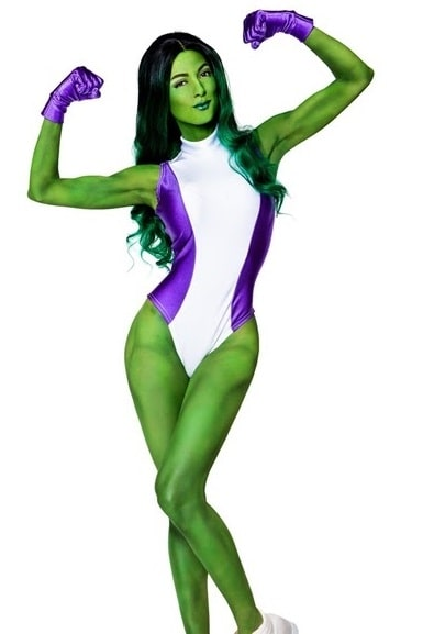 A woman in a She-Hulk costume, with the white and purple Spandex suit and green body paint.