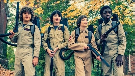 Dustin, Mike, Will, and Lucas in their Ghostbusters Halloween costume, complete with one-piece utility wear and proton packs in Stranger Things.
