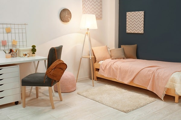 A dorm room with pink sheets, wooden furniture, and dark gray walls.
