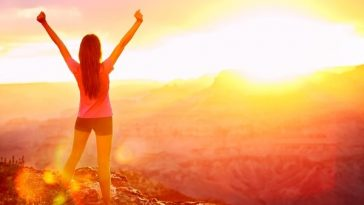 A girl standing on top of a hiking trail with her arms outstretched, facing the sun.