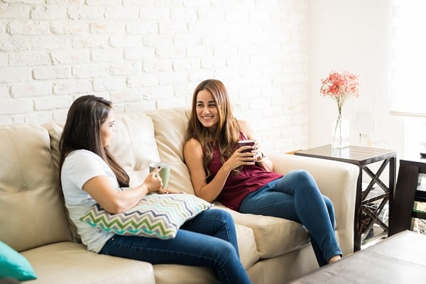 Two girls having coffee on the couch, while giving each other friendly advice.