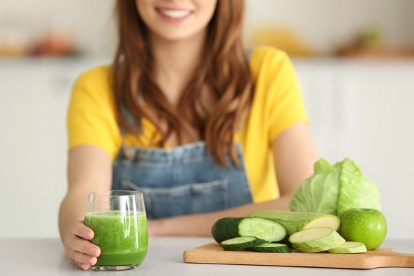 A young woman in a yellow shirt and denim jumpsuit, holding a glass of fresh green juice.