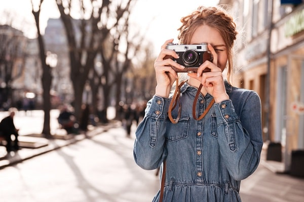 A girl in a denim outfit, pointing her vintage camera and shooting photos out on the street.