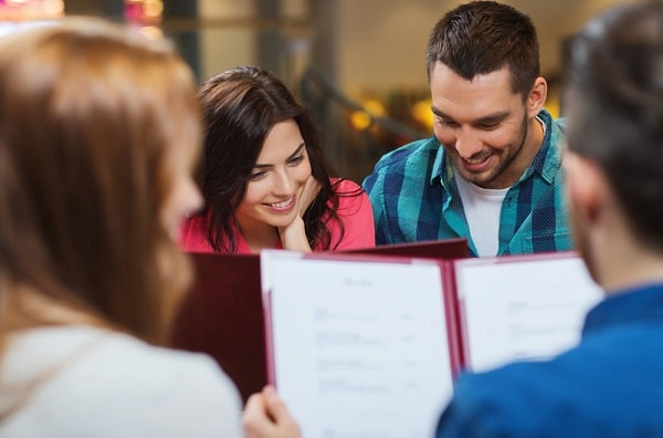 A group of friends in a restaurant, checking out the menu.