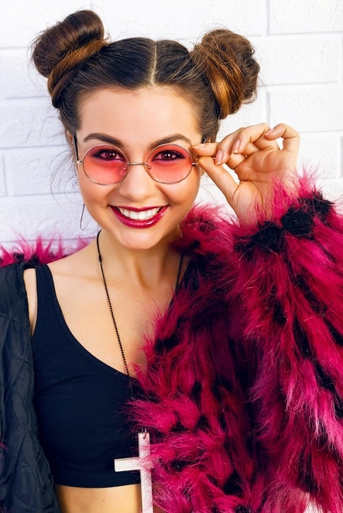 A stylish girl in a magenta faux fur coat, tinted sunglasses, and hair tied into a double bun.