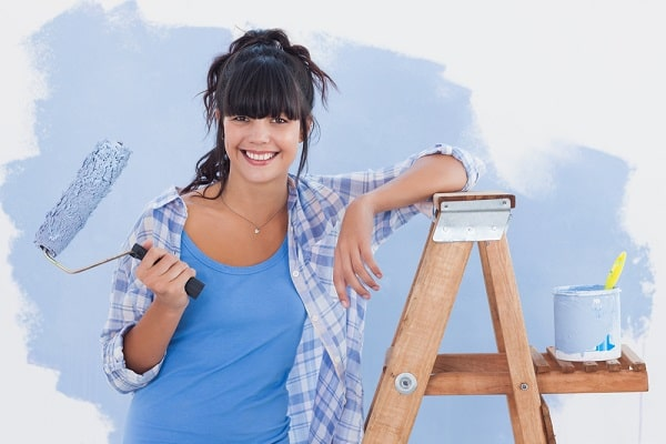 A girl leaning against a step ladder, holding a paint brush, with a partially painted dorm room wall at the back.